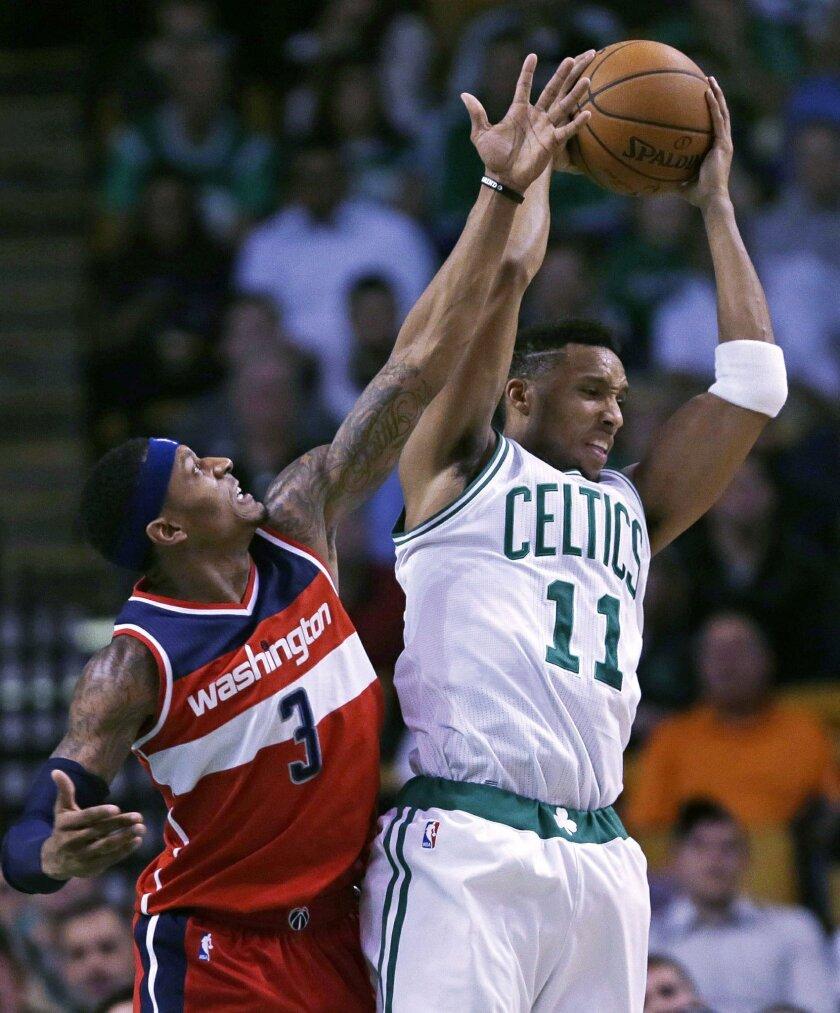 Boston Celtics guard Evan Turner (11) grabs a rebound against Washington Wizards guard Bradley Beal (3) during the first quarter of an NBA basketball game in Boston, Friday, Nov. 6, 2015. (AP Photo/Charles Krupa)