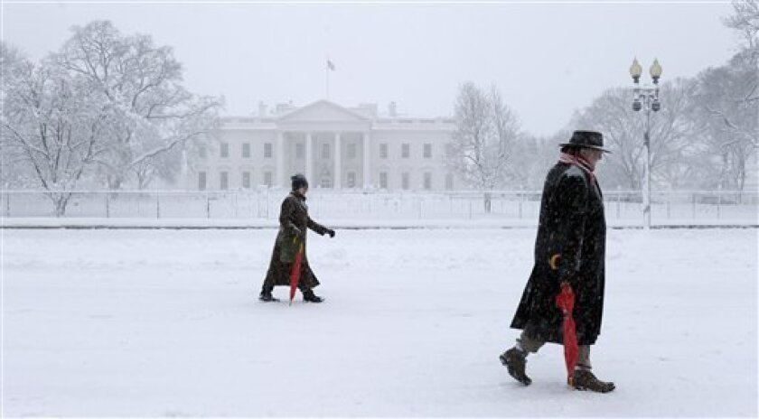 Pedestrians walk past the White House in Washington, Saturday, Feb. 6, 2010, as snow continued to fall in the Washington area. (AP Photo/Susan Walsh)