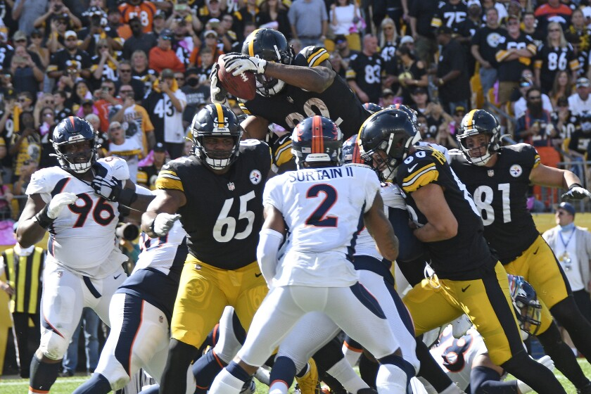 Pittsburgh Steelers running back Najee Harris, top, leaps over the goal line for a touchdown during the first half of an NFL football game against the Denver Broncos in Pittsburgh, Sunday, Oct. 10, 2021. (AP Photo/Don Wright)