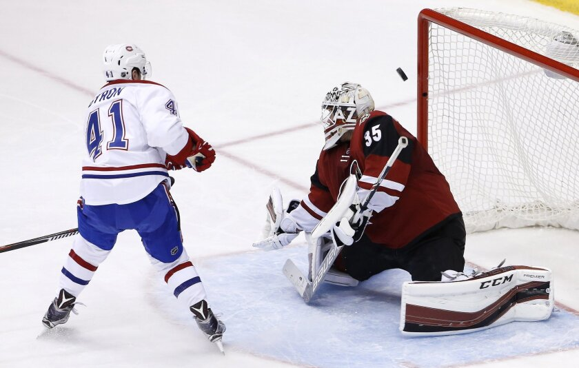 Montreal Canadiens' Paul Byron (41) sends the puck off the post behind Arizona Coyotes' Louis Domingue (35) during the second period of an NHL hockey game Monday, Feb. 15, 2016, in Glendale, Ariz. (AP Photo/Ross D. Franklin)