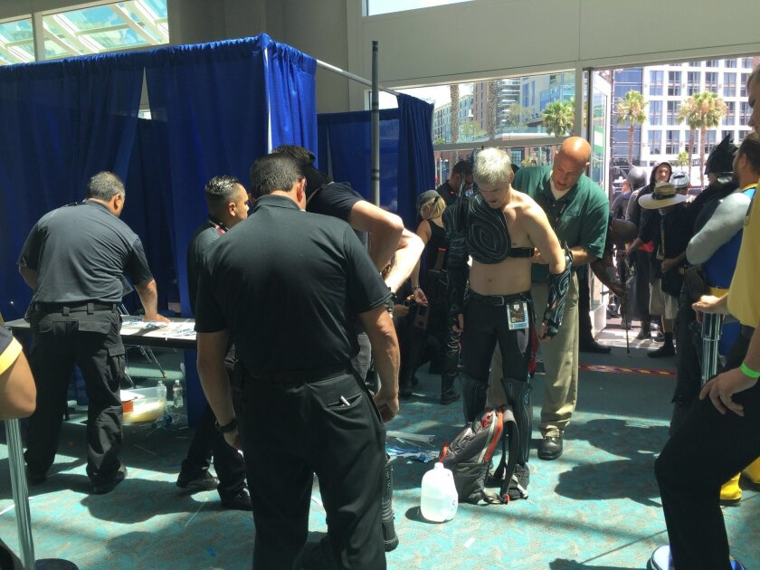 Comic-Con security checks a man's weapons and secures them to his costume Thursday.
