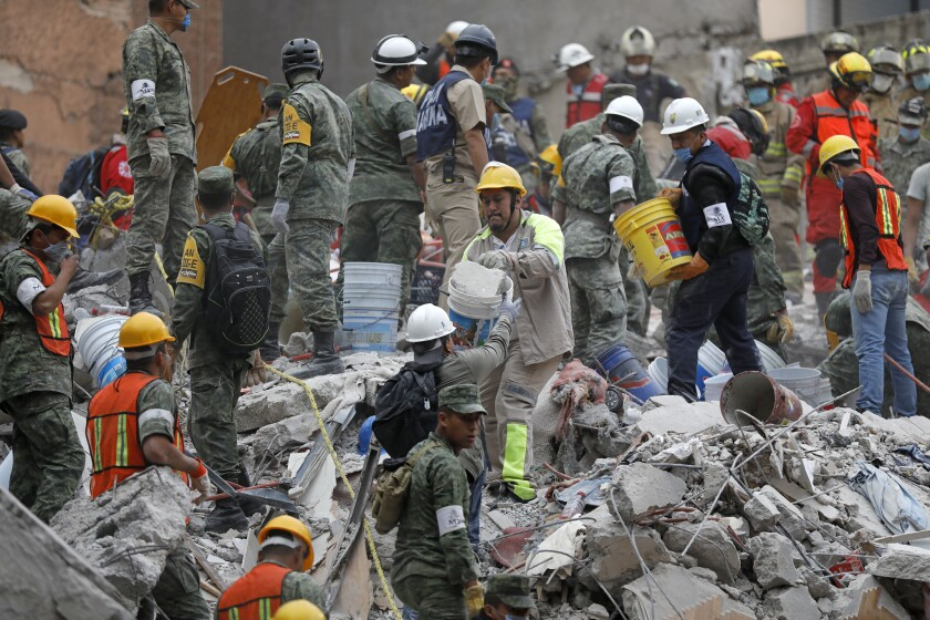 Search and rescue teams remove rubble at a collapsed six-story residential building in Mexico City.