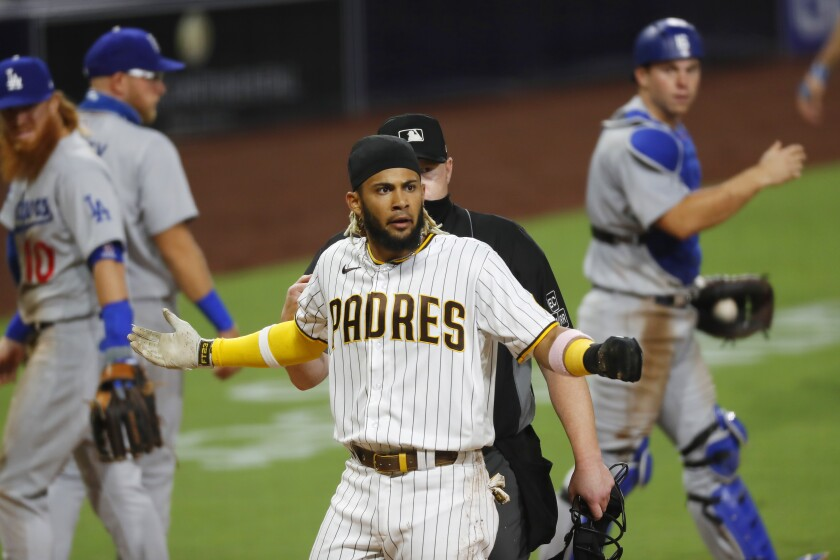 Padres' Fernando Tatis Jr. reacts after colliding with Dodgers catcher Will Smith at home plate after a rundown Monday.