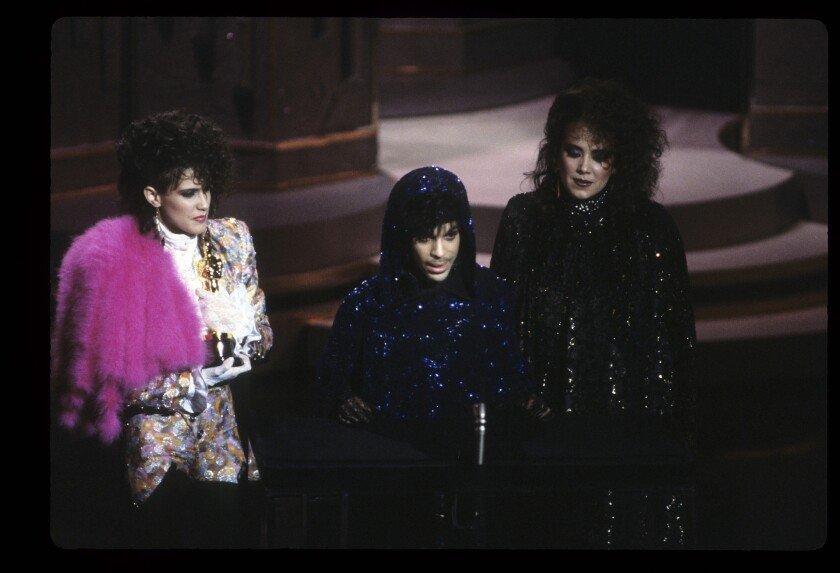 Prince, draped in purple, accepts his 1985 Academy Award for original score flanked by Wendy Melvoin, left, and Lisa Coleman.