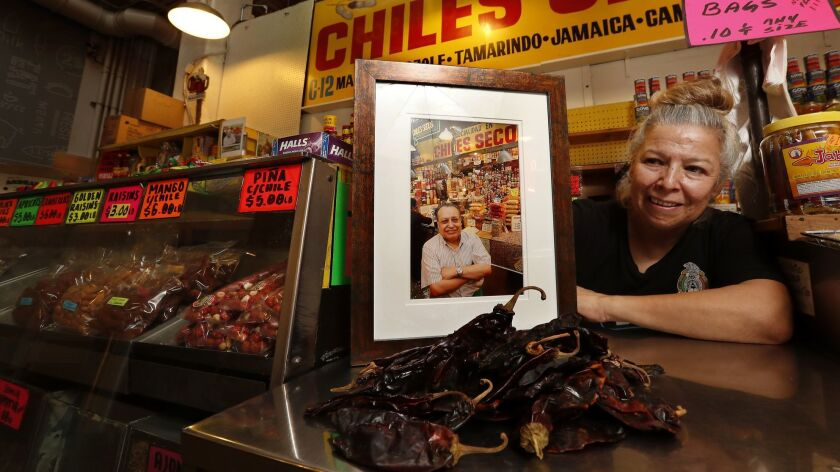 Rocio Lopez next to a photograph of her father, Celestino Lopez, at the Chiles Secos stand inside Grand Central Market. Celestino started working at the market in 1970 and eventually bought the stand, which he later passed on to his family.