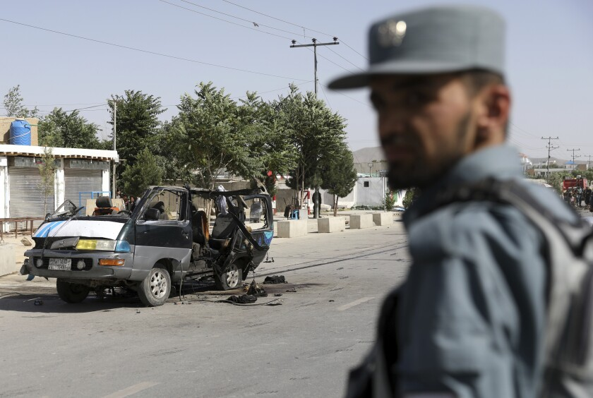 An Afghan security personnel inspect the site of a bomb explosion in Kabul, Afghanistan, Thursday, June 3, 2021. Police say a bomb has ripped through a minivan in the western part of the Afghan capital Kabul, killing at least four people. No one took responsibility for the attack in the neighborhood, which is largely populated by the minority Hazara ethnic group who are mostly Shiite Muslims. (AP Photo/Rahmat Gul)