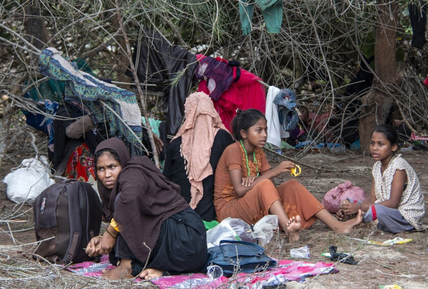 Ethnic Rohingya people rest on a beach after their boat was stranded on Idaman Island in East Aceh, Indonesia, Friday, June 4, 2021. Villagers in Indonesia's Aceh province discovered a stranded boat carrying dozens of Rohingya Muslims, including children, who had left a refugee camp in Bangladesh, officials said. (AP Photo/Zik Maulana)
