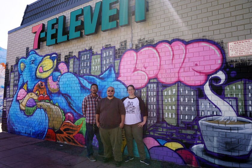 "From left: Co-founder of Love City Heights Carlos Quezada, artist GMONIK and Danielle Iwatsu stand in front of the ""Bear Essentials"" mural on the wall of a 7-Eleven in City Heights on Oct 1, 2019."