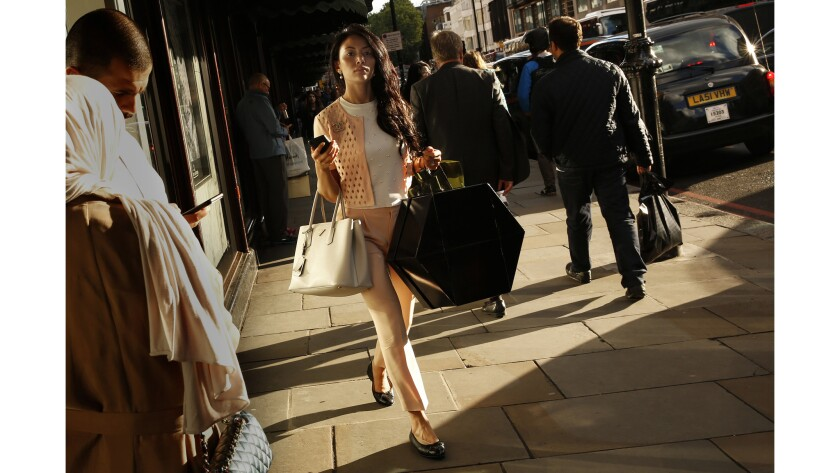 A young woman carries packages outside Harrods, one of London's internationally known stores.