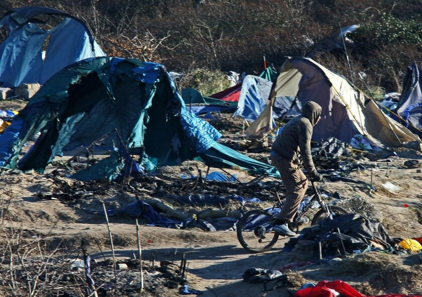 A migrants rides with his bicycle in the Calais refugee camp, northern France Tuesday, Jan. 19, 2016. The bulldozers were used to clear a 100-meter-long strip of land between the camp and the highway. Up to 6,000 people were staying there in the fall, though the number has decreased recently. (AP Photo/Michel Spingler)