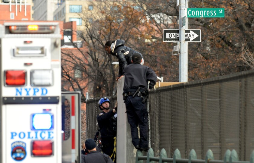 The woman climbed over the railing on the Congress St. sign pole, which crosses over the Brooklyn-Queens Expressway, around 10:30 a.m., police said. Cops found her with her legs dangling above the busy expressway.