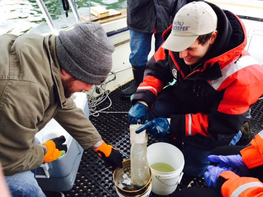 In this March 31, 2015 photo provided by NY/NJ Baykeeper, Mitchell Mickley left, and Justin Procopio process samples of water just collected from New York Harbor near the Statue of Liberty. A report by NY/NJ Baykeeper, says the waterways surrounding New York City are a soup of plastic, ranging from
