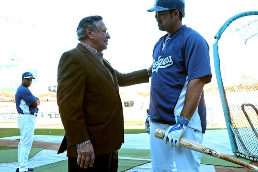 Announcer Jaime Jarrin chats with Dodgers first baseman Adrian Gonzalez on the field before a playoff game at Dodger Stadium in 2013.