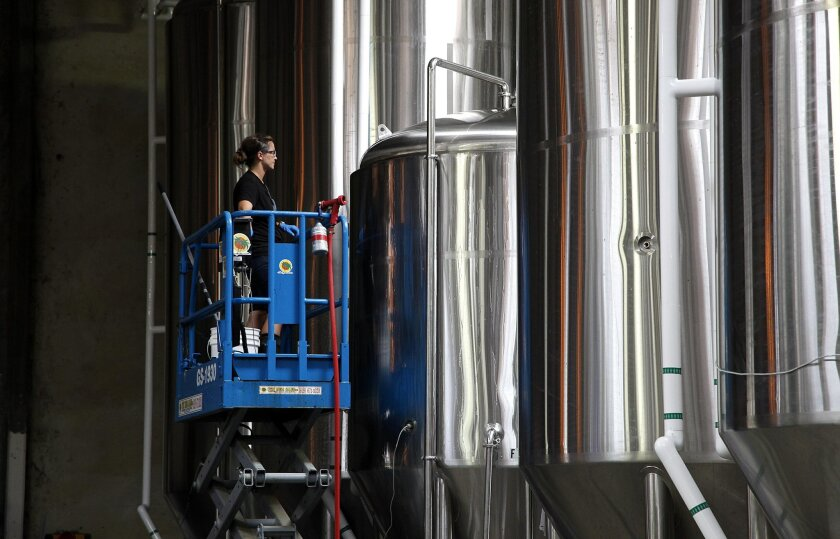 Molly Ross inspects the brewing machinery at St. Archer Brewing Company located on Distribution Avenue in Miramar.