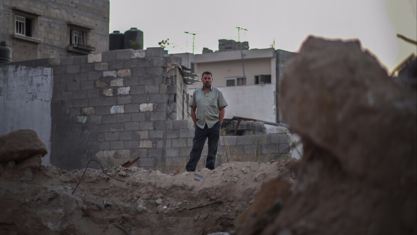 Nashat Nawati stands over the rubble of his home, which was destroyed by Israel in the last Gaza war.