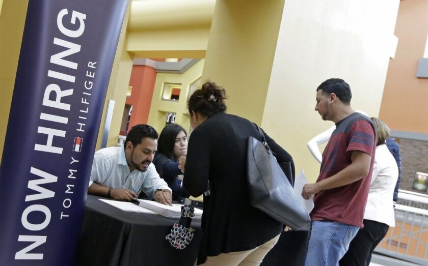 In this Tuesday, Oct. 3, 2017, file photo, job seekers stand at a booth at a job fair at the Dolphin Mall in Sweetwater, Fla.