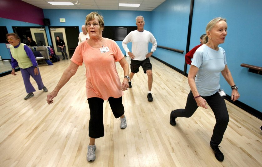 Nancy Porter, left and Gerry Halpern lunge in a class at the Toby Wells YMCA as part of a study on how to avoid age-related mental decline.