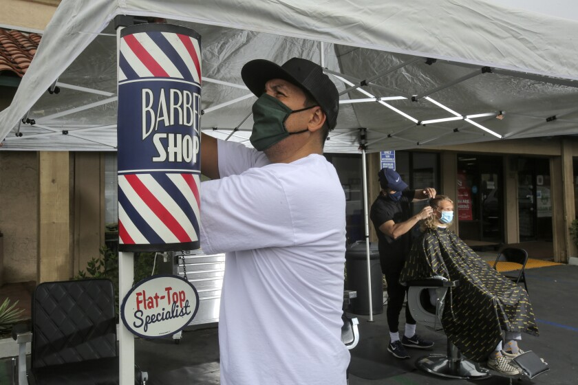JR Medina, owner of JR's Barbershop in San Marcos, puts up a sign saying he is open for business.