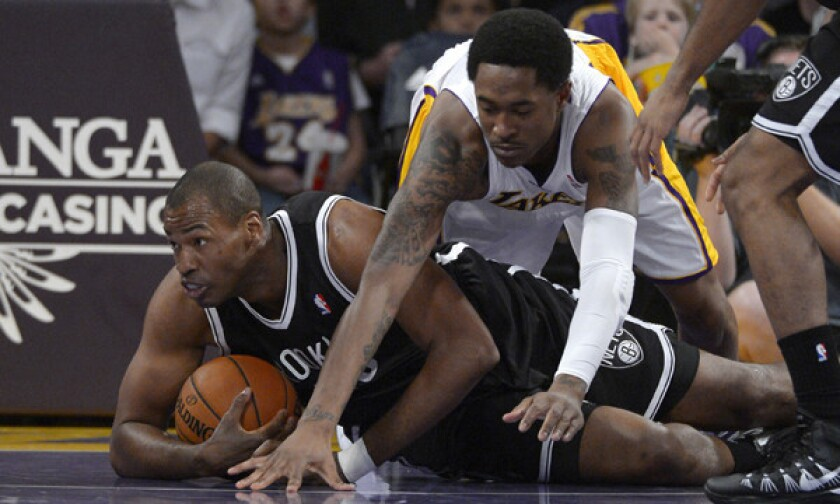 Brooklyn Nets center Jason Collins, left, battles for a loose ball with Lakers guard MarShon Brooks during the first half of Sunday's game at Staples Center.
