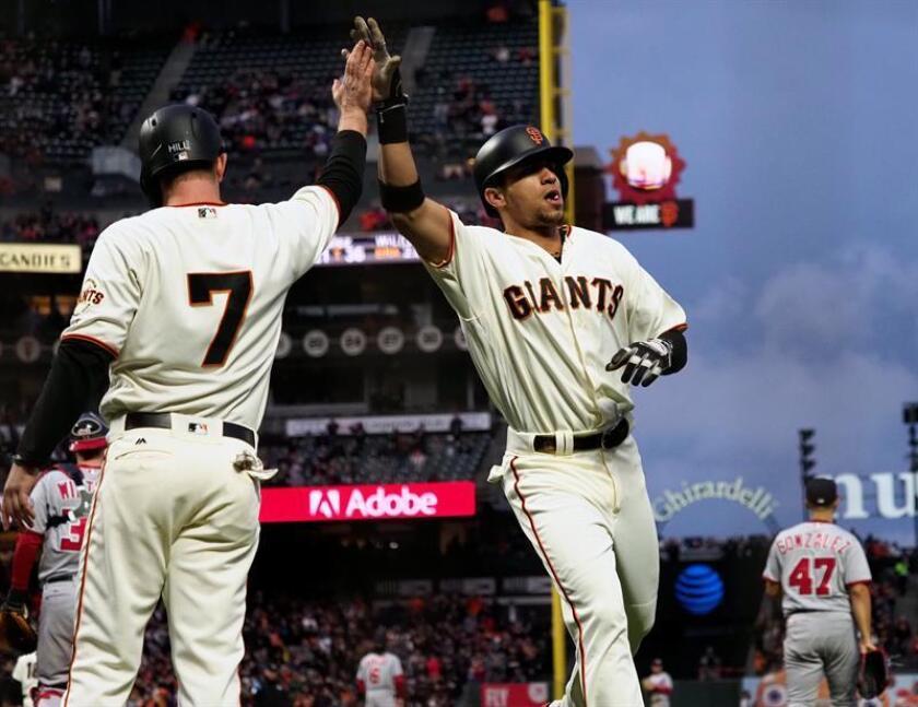 El jugador Gorkys Hernandez (d) de los Gigantes de San Francisco saluda a un compañero durante un juego. EFE/Archivo