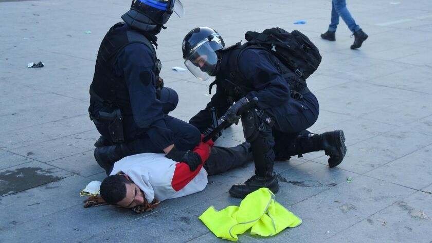 """Police forces arrest a protester on Feb. 16, 2019, in Bordeaux, France, during the 14th consecutive week of nationwide """"yellow vest"""" protests against the French president's policies."""
