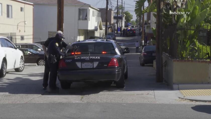 San Diego police work next to a patrol car