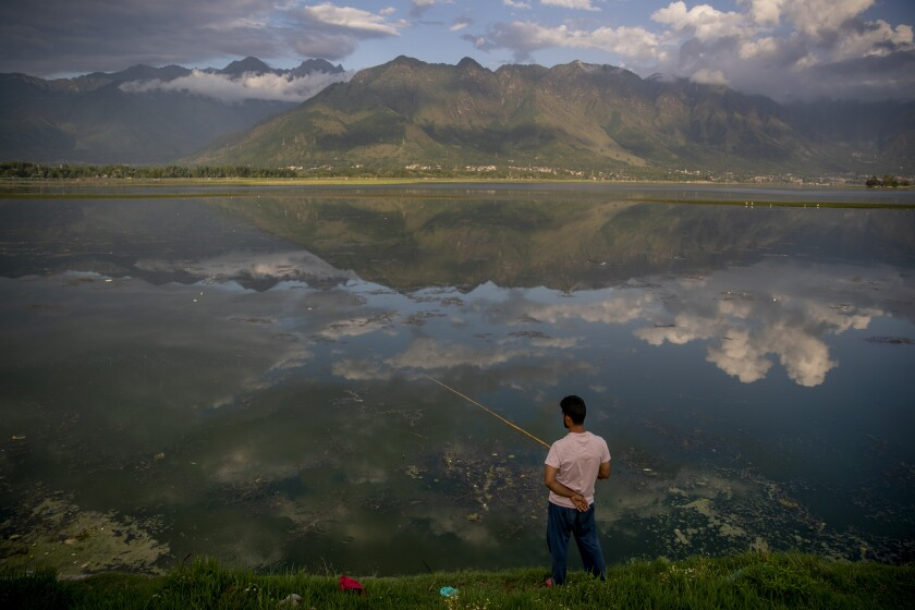 Clouds are reflected in water as a Kashmiri man fishes in the Dal Lake on the outskirts of Srinagar, Indian controlled Kashmir, Friday, July 30, 2021. (AP Photo/Dar Yasin)
