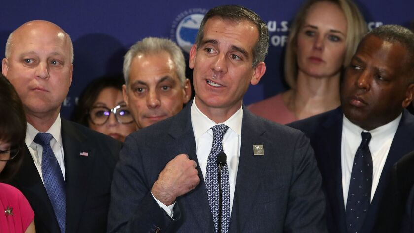 Los Angeles Mayor Eric Garcetti, flanked by others mayors, speaks at a news conference Wednesday, at which several mayors explained why they were not attending a White House meeting on infrastructure.