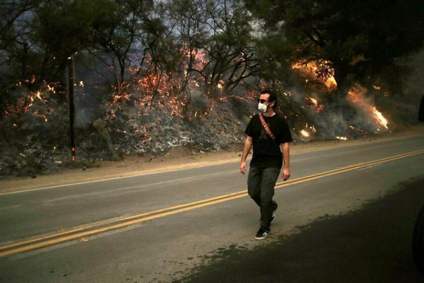 Un hombre pasa frente a un área afectada por el incendio Thomas en Ojai (EE.UU.). EFE/Archivo