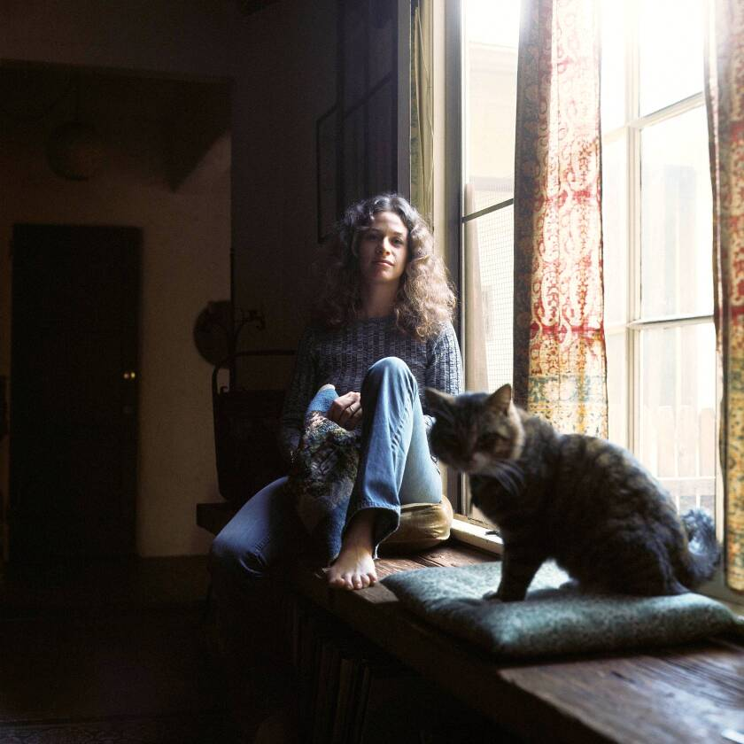 Carole King sits next to a window, with a cat.