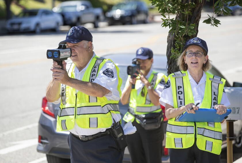 Two people hold speed radar guns up to their faces while a third holds a clipboard
