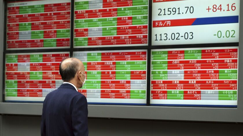 A man looks at an electronic stock board showing Japan's Nikkei 225 index at a securities firm in To