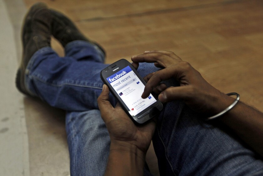 In this 2012 file photo, a man surfs the Facebook site on his mobile phone in Mumbai, India.