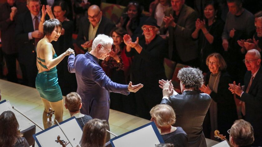 """Composer John Adams takes his bows flanked by pianist Yuja Wang and Los Angeles Philharmonic conductor Gustavo Dudamel on Thursday night at Walt Disney Concert Hall, where they premiered Adams' concerto """"Must the Devil Have All the Good Tunes?"""""""