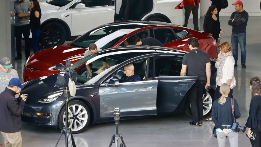 People check out the Tesla Model 3 at the Westfield Century City showroom Friday morning.