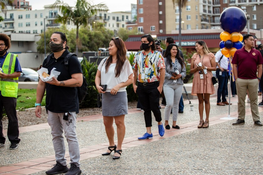 """People, some wearing masks, wait in line to get free coffee during the """"Back Together San Diego County"""" event."""