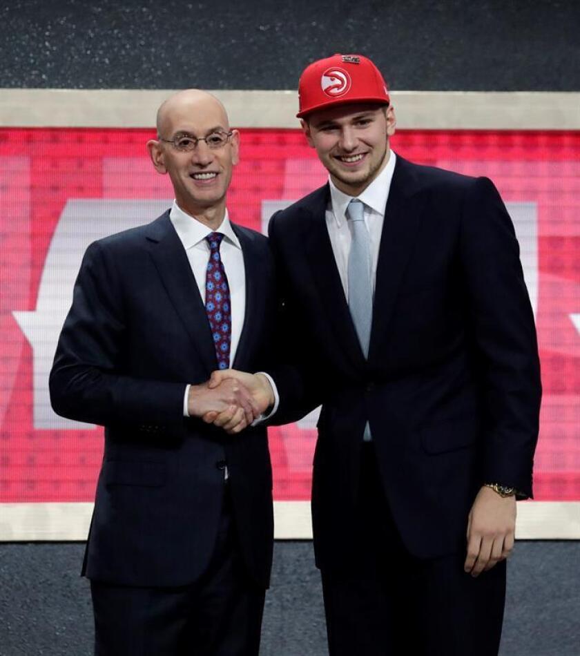 El comisionado de la NBA, Adam Silver (i) se da la mano con Luka Doncic (d) de Eslovenia, elegido número tres por los Atlanta Hawks en la primera ronda del draft de la NBA 2018, en el Barclays Center en Brooklyn, Nueva York (EE.UU.). EFE