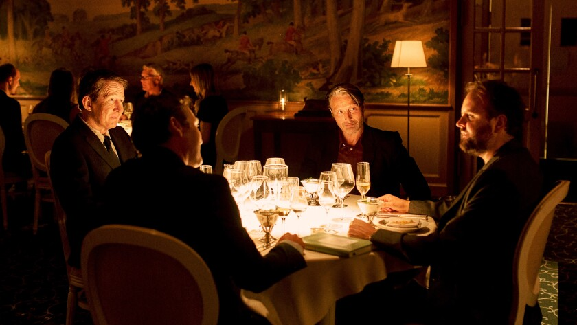 A group of men share a meal in an elegant restaurant.