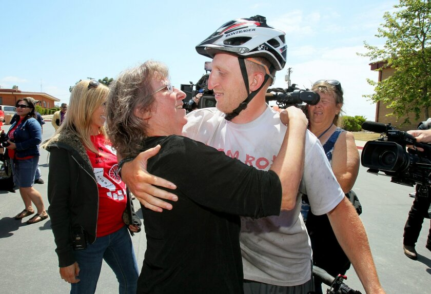 Ex-Marine Rob Jones, who lost both of his legs in Afghanistan, hugs his mom Carol Miller as he arrives at the finish of his cross county bicycle journey to a celebration for him at the Camp Del Mar area of the base.
