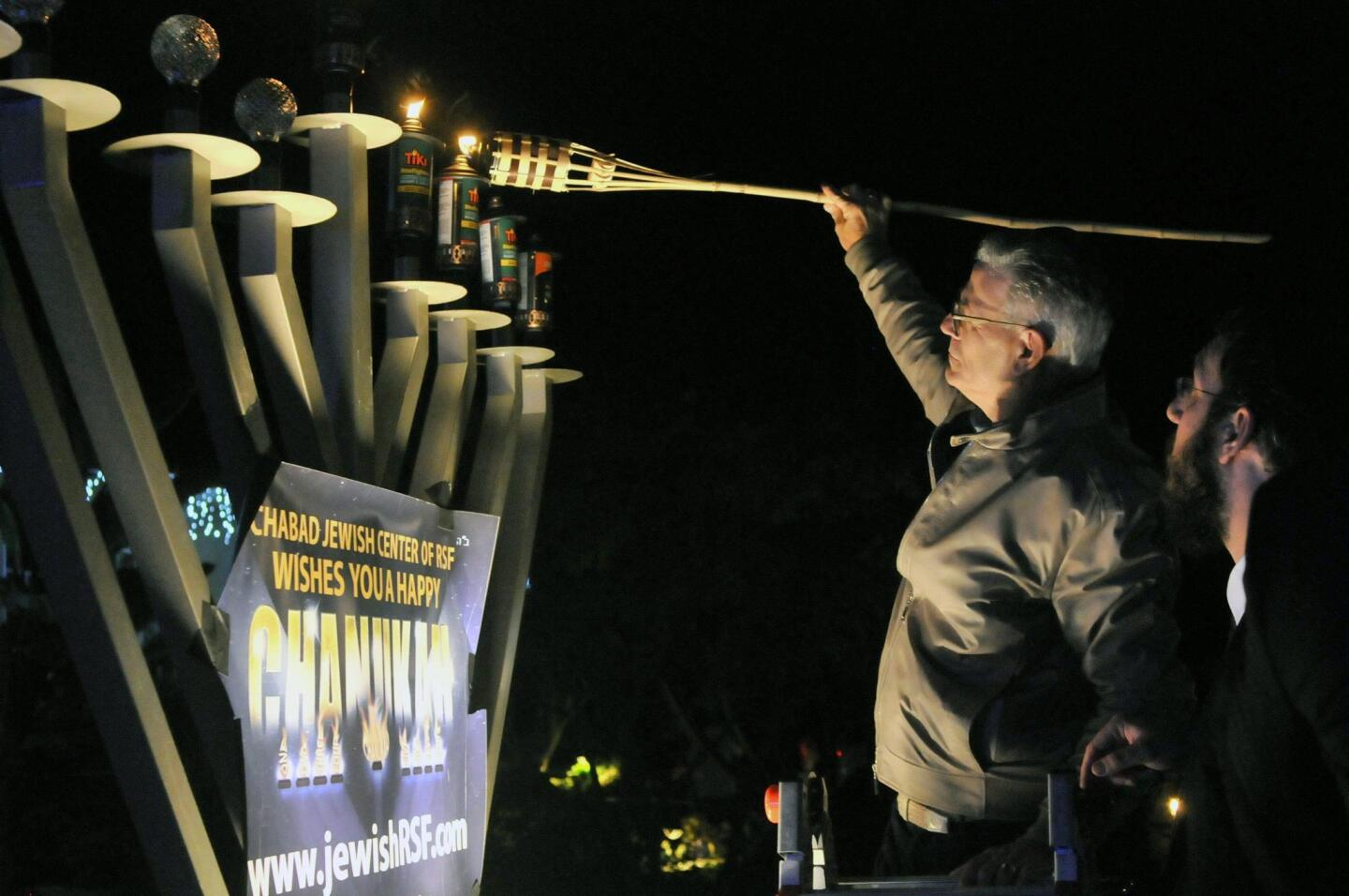 Charles Wax lights the Menorah as Rabbi Levi Raskin looks on