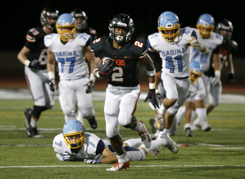 Huntington Beach High running back Arick McLawyer breaks a long run to set up a touchdown in the second quarter of a nonleague game against Marina at Cap Sheue Field on Sept. 14, 2018.