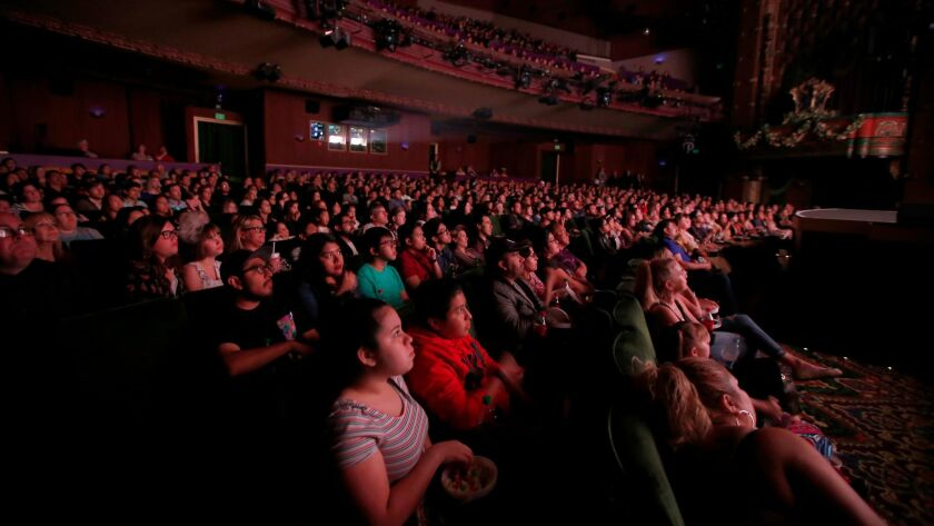 """The audience at Hollywood's El Capitan Theatre watches """"Beauty and the Beast"""" on Thursday night."""