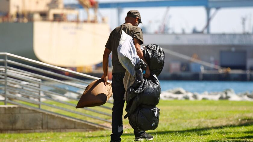 """Usiel Oceguera, who is homeless, gathers his belongings in Embarcadero Marina Park South. """"You are never safe when you're out in the open."""""""