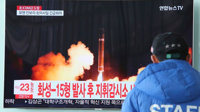 A man watches a TV screen showing what the North Korean government calls the Hwasong-15 intercontine