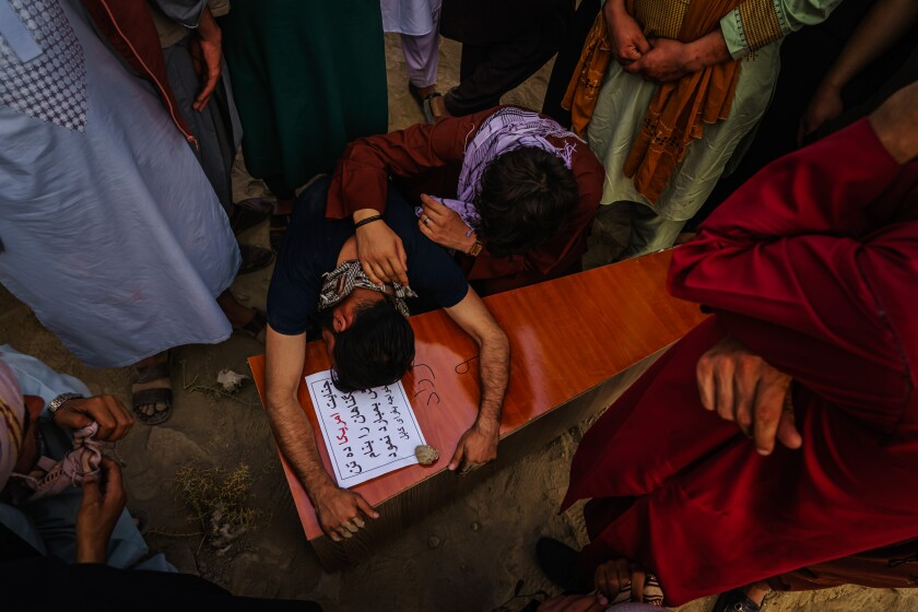 KABUL, AFGHANISTAN -- AUGUST 30, 2021: A relative throws himself and weeps over the casket of Farzad, 12, who was killed by U.S. drone airstrikes, according to the family, in Kabul, Afghanistan, Monday, Aug. 30, 2021. (MARCUS YAM / LOS ANGELES TIMES)