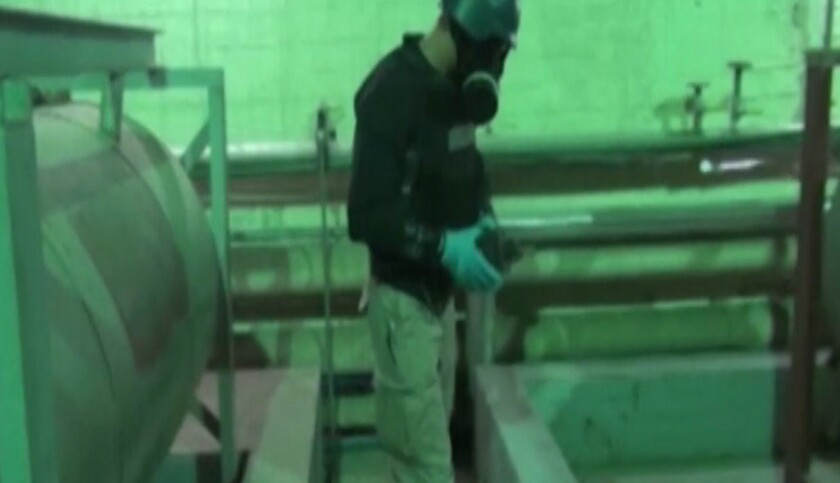 An image taken from Syrian television shows an inspector from the Organization for the Prohibition of Chemical Weapons at work at an undisclosed location in Syria on Tuesday.