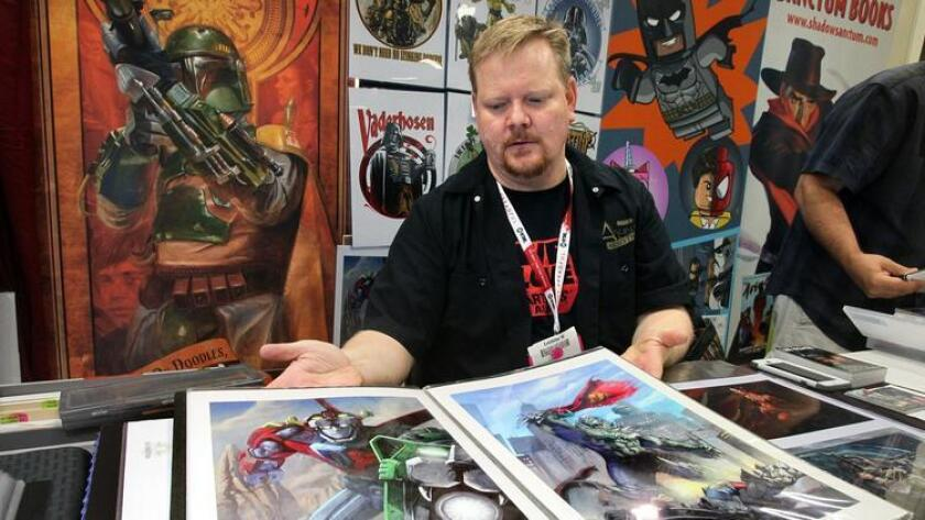 Comic Con day 2- San Diego artist Lee Kohse pages through a book of his work at his booth at the Artist's Alley area.