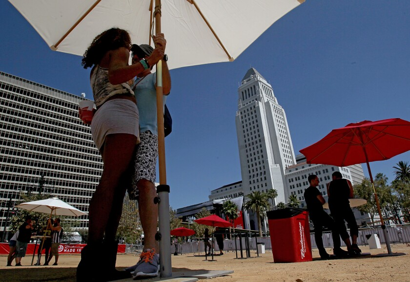 Whittier residents Robert and Heydi Cortner seek out some shade as they wait for performances to begin at the Made In America Festival in downtown Los Angeles on Sunday, Aug. 31, 2014.