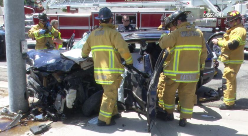 Chula Vista firefighters work to free a man trapped inside a crashed car Wednesday afternoon at Otay Lakes Road and Rutgers Avenue. Chula Vista police said the man was the suspect in a credit union robbery who was fleeing from police when he collided with a truck.