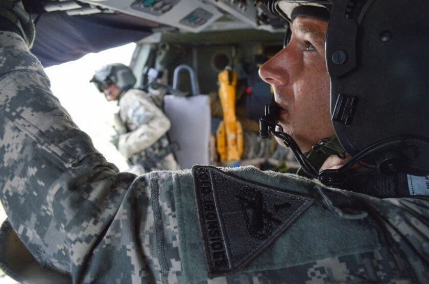 Sgt. 1st Class Scott P. Campbell selects a radio to privately instruct a crew member during flight. Photo courtesy U.S. Army